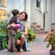 Little boy giving flower to his mom — Stockfoto