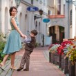 Young mother and her son walking outdoors in city — Stock Photo