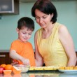 Young mother and her little son baking muffins - Stock Photo