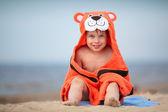 Schattige kleine jongen dragen tijger handdoek buitenshuis — Stockfoto
