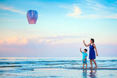 Young mother and son flying fire lantern together — Stock Photo