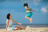 Young mother and son having fun on the beach — Stock Photo