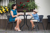Mother and son sitting in outdoor cafe — Stock Photo