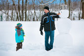 Little boy with his father making a snowman — Stock Photo