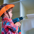 Cute little boy using an electric screwdriver — Stock Photo