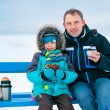 Happy father and son picnicking on winter beach — Stock Photo