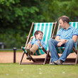 Happy father and son having rest in city park — Lizenzfreies Foto