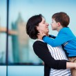Loving mother and son hugging outdoors in city — Stock Photo