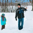 Little boy with his father making a snowman — ストック写真