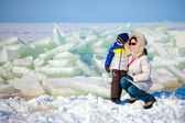 Young mother and her son on icy beach — Stock Photo