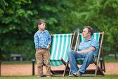 Feliz pai e filho, tendo o resto no parque da cidade — Fotografia Stock