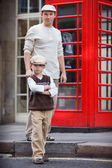 Happy father and son outdoors by red phone booth — Stock Photo