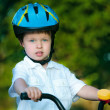 Close up portrait of a cute little boy on bicycle — Stock Photo
