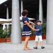 Young mother and her son playing outdoors in city — Stockfoto