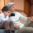 Father and little son holding retro camera in city — Stock Photo #38806151