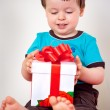 Happy toddler boy opening a gift box — Stock Photo