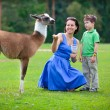 Young woman and her little son feeding baby lama — Stock Photo #38806479