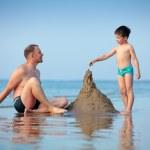unga far och hans son byggnad sand castle — Stockfoto