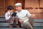 Father and little son with retro camera outdoors — Stock Photo