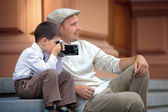 Father and little son holding retro camera in city — Stock Photo