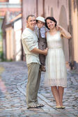 Young family of three in city street — Stock Photo