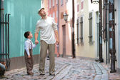 Father and son walking outdoors in city — Stock Photo