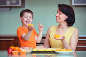 Smiling young mother and son baking muffins — Stock Photo