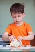 Five year old boy helps his mother make cookies — Stock Photo
