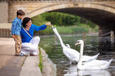 Young mother and son feeding swans at the lake — Stock Photo