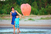 Young mother and son flying fire lantern together — Stok fotoğraf