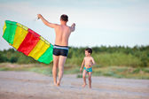 Young father and his son playing with kite — Stok fotoğraf
