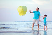Happy father and son flying fire lantern together — Stok fotoğraf