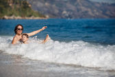 Mother and son splashing in ocean waves — Stock Photo