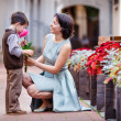 Stock Photo: Little boy giving flower to his mom