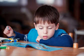 Concentrated child reading a manual — Stock Photo
