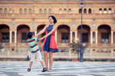 Young mother and her son playing outdoors in city — Stock Photo