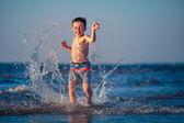 Little boy running through the water at beach — Stock Photo