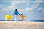 Family with yellow balloons on the beach — Photo
