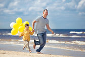 Family with yellow balloons playing on the beach — Stock Photo