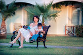 Happy mother and son sitting outdoors — Stock Photo