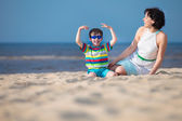 Mother and son enjoying time at tropical beach — Stock Photo