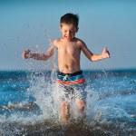 Little boy running through water at the beach — Stock Photo