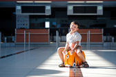 Cute little boy with orange suitcase at airport — Stock Photo