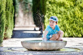 Boy having fun with fountain shot during summer time — Stock Photo