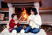 Mother and her little son by a fireplace — Stock Photo