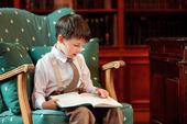 Cute little boy reading book on armchair — Stockfoto