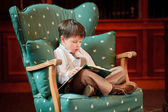 Cute little boy reading book on armchair — Photo
