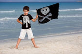 Cute boy dressed as pirate on tropical beach — Stock Photo