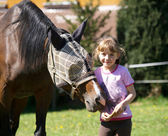 Girl giving titbit to horse — Stock Photo