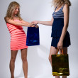 Foto Stock: Two girls with paper packages for purchases